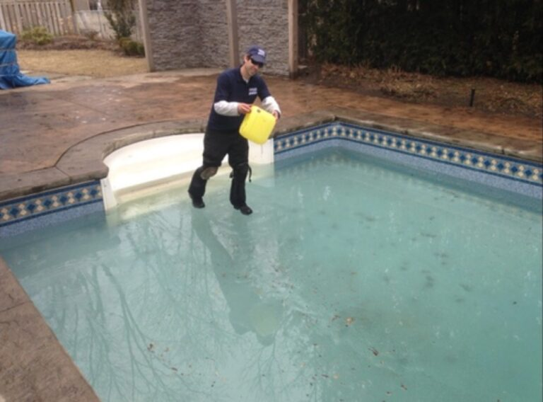 pool maintenance guy adding chlorine to a pool